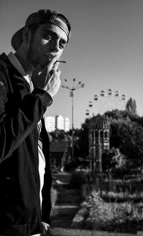 Black and white young male in casual wear and cap smoking cigarette while standing in city park against observation wheel