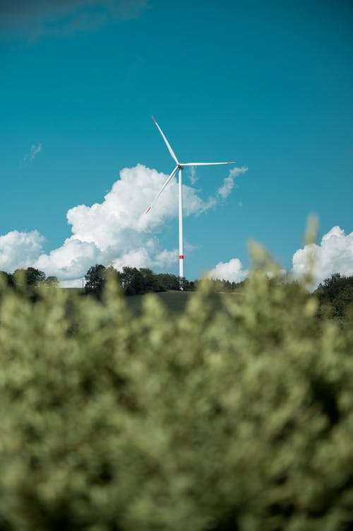 White Wind Turbine Through Green Grass
