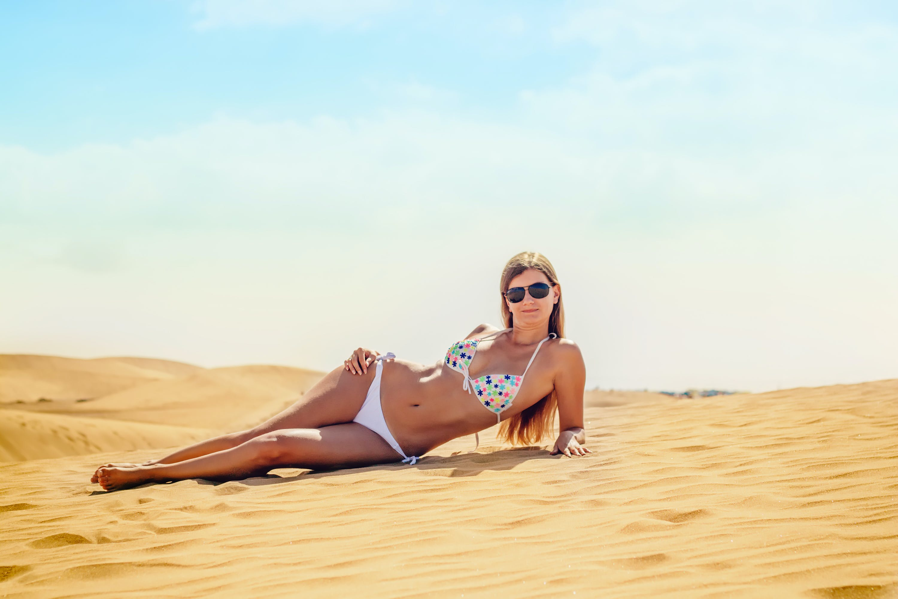 Woman Wearing Blue and White Bikini Lying on Desert