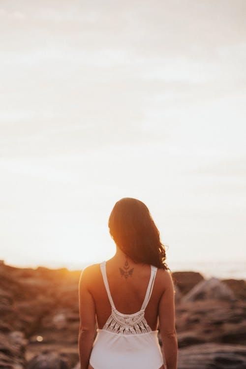 日の出に直面して立っている女性