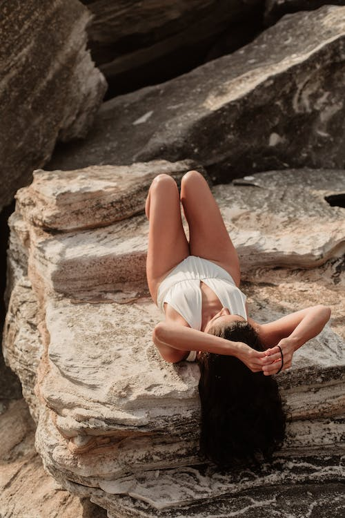 Woman Lying On A Rock With Hands Up