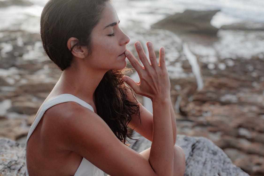 Woman Wearing White Tank Top Meditating