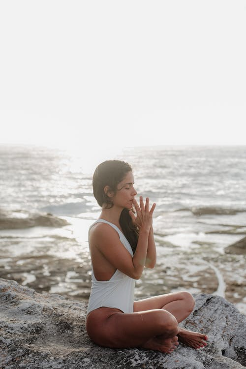 Woman Wearing White Swimsuit Meditating on Mountain