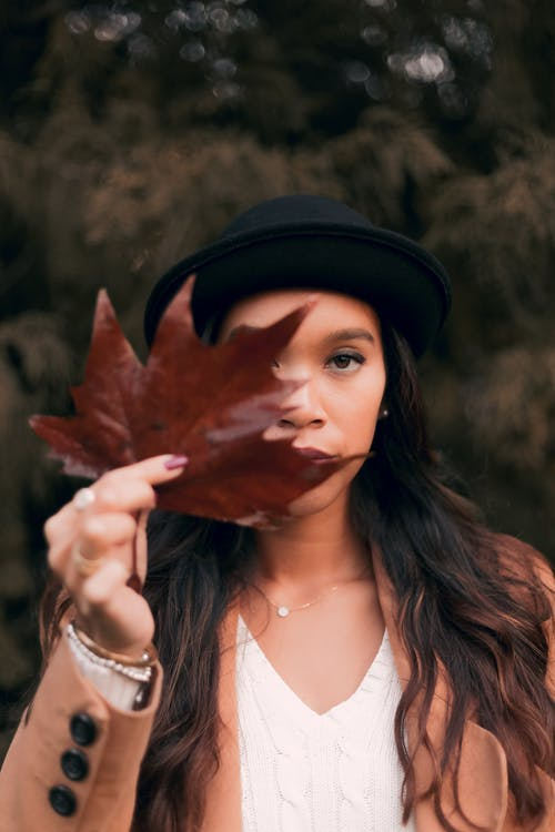 Woman Wearing Brown Coat and Black Hat While Holding Brown Maple Leaf