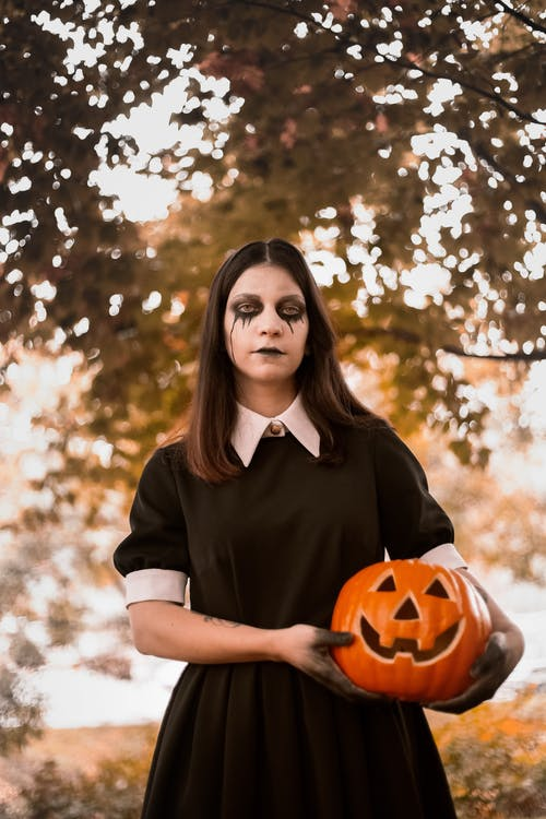 Woman Wearing Black and White Collared Dress With Halloween Makeup Holding Jack-o'-lantern Near Green Leaf Tree