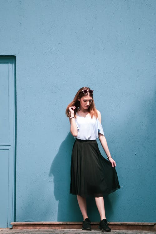 Woman Standing by the Blue Wall