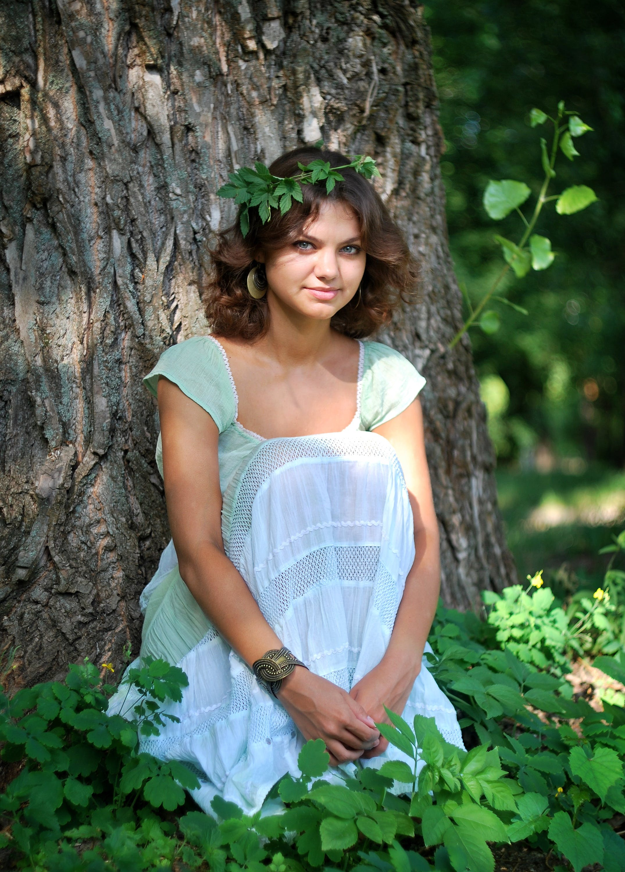Smiling Woman Wearing Green Leaf Crown With Green and White Sleeveless Dress Sitting in Green Leaf during Day Time