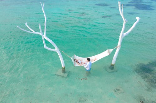 Person Lying on White Hammock