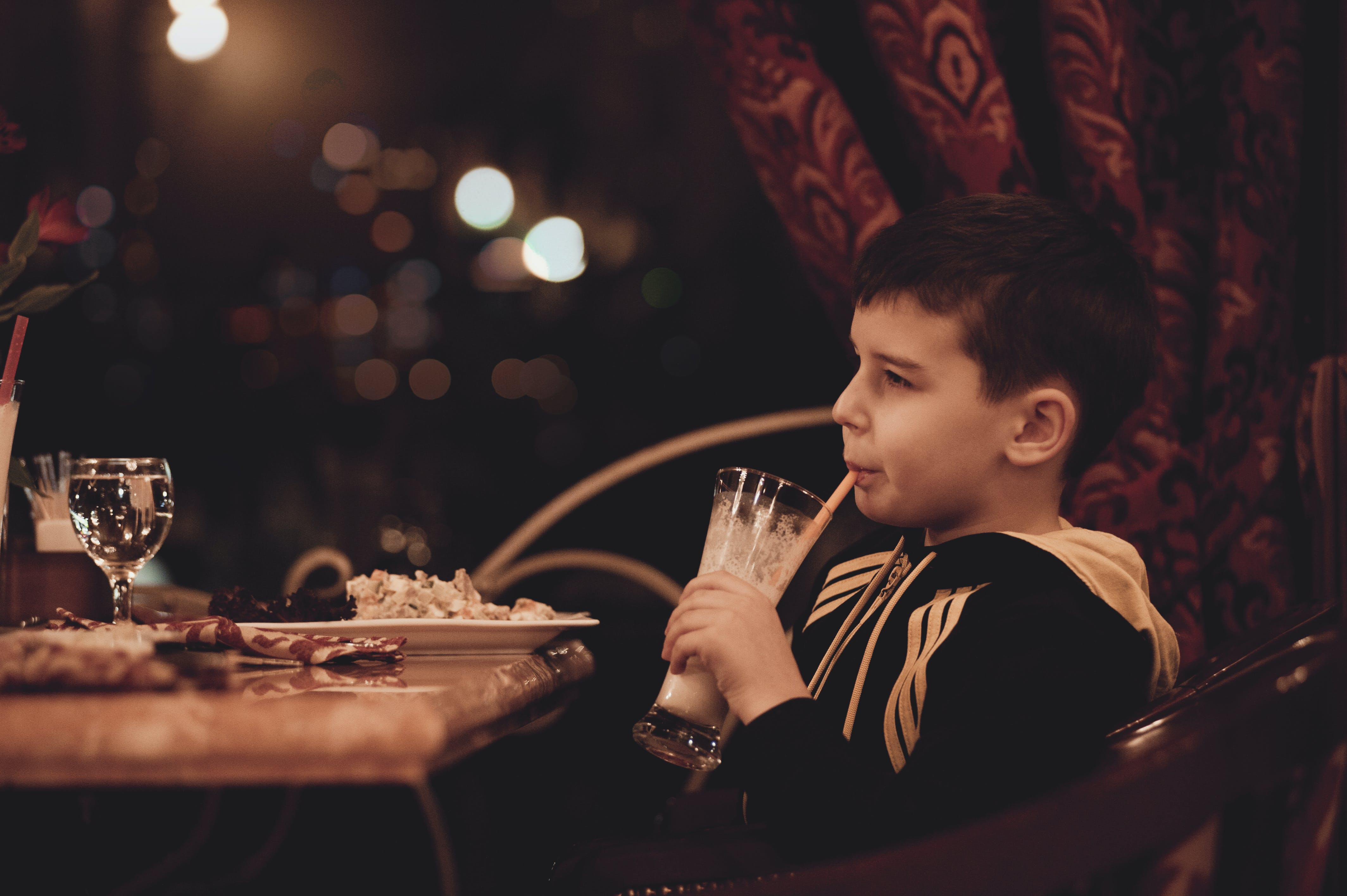 Boy Holding Drinking Glass Sitting in Front of Table