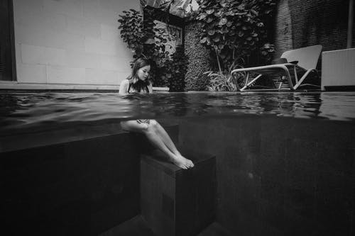 Grayscale Photography of Woman Sitting Under Water
