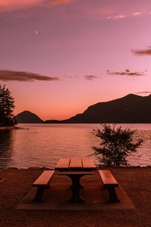 Brown Wooden Table and Bench Near Body of Water during Sunset