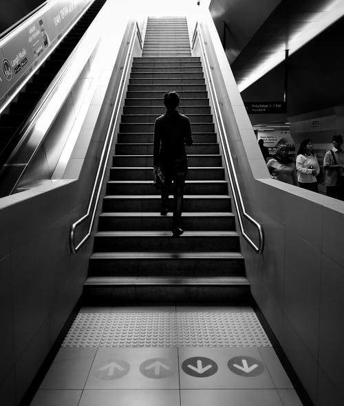 Grayscale Photography of Person Walking on Stairs