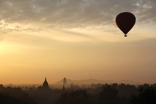 Hot Air Balloon and City Silhouette during Daytime