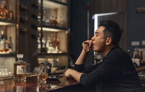 Asian man resting in bar with cigar and whiskey