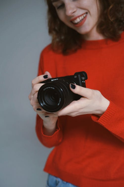 Woman Holding a Black Dslr Camera