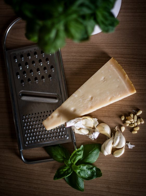 Sliced Cheese Beside Garlic, Basil and Cheese Grater on Table