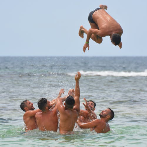 Group of Men in Body of Water