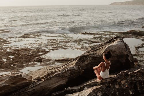 Photo Of Woman Sitting On Rock