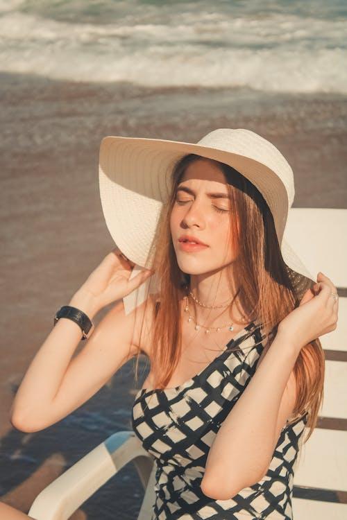 咖啡色頭髮的女人, 坐, 太阳椅, 太陽帽 的 免费素材照片