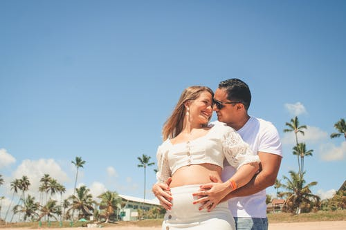 Delighted pregnant couple embracing and touching belly on beach