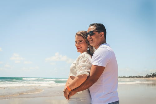 Side view smiling pregnant couple in stylish white outfits embracing and touching belly while standing on sandy beach in exotic resort