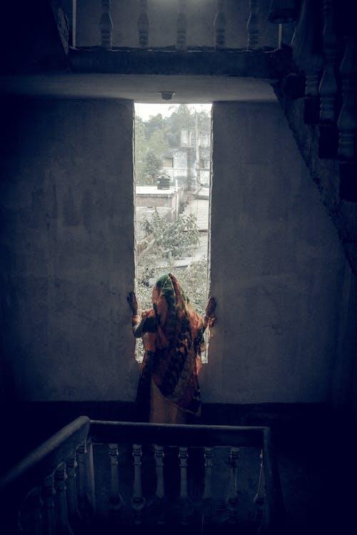 Photo Of Woman Sneaking Through Window