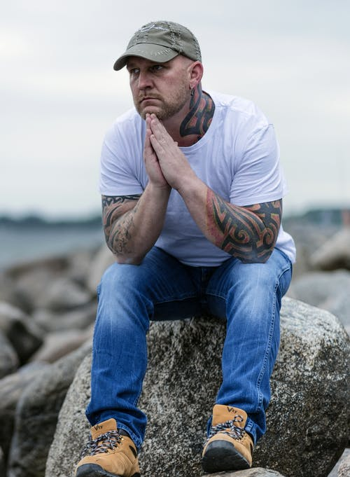 Man Sitting on Gray Rock on Selective Focus Photo