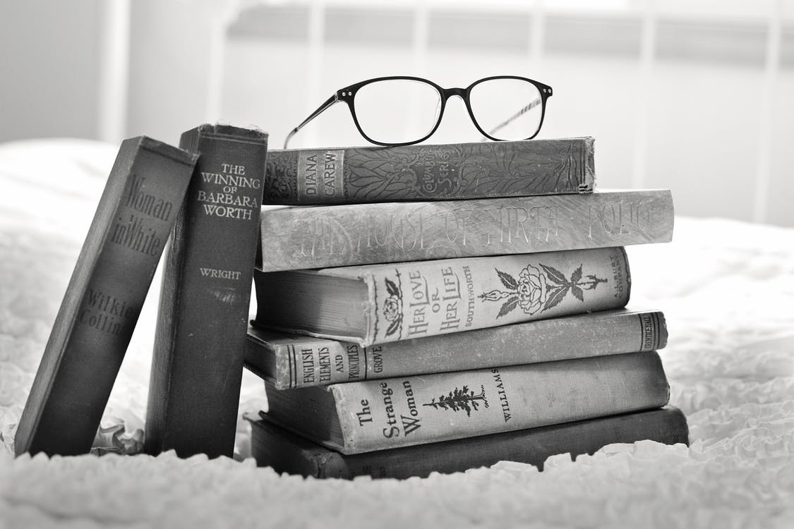 Grayscale Photo of Eyeglasses on Pile of Books