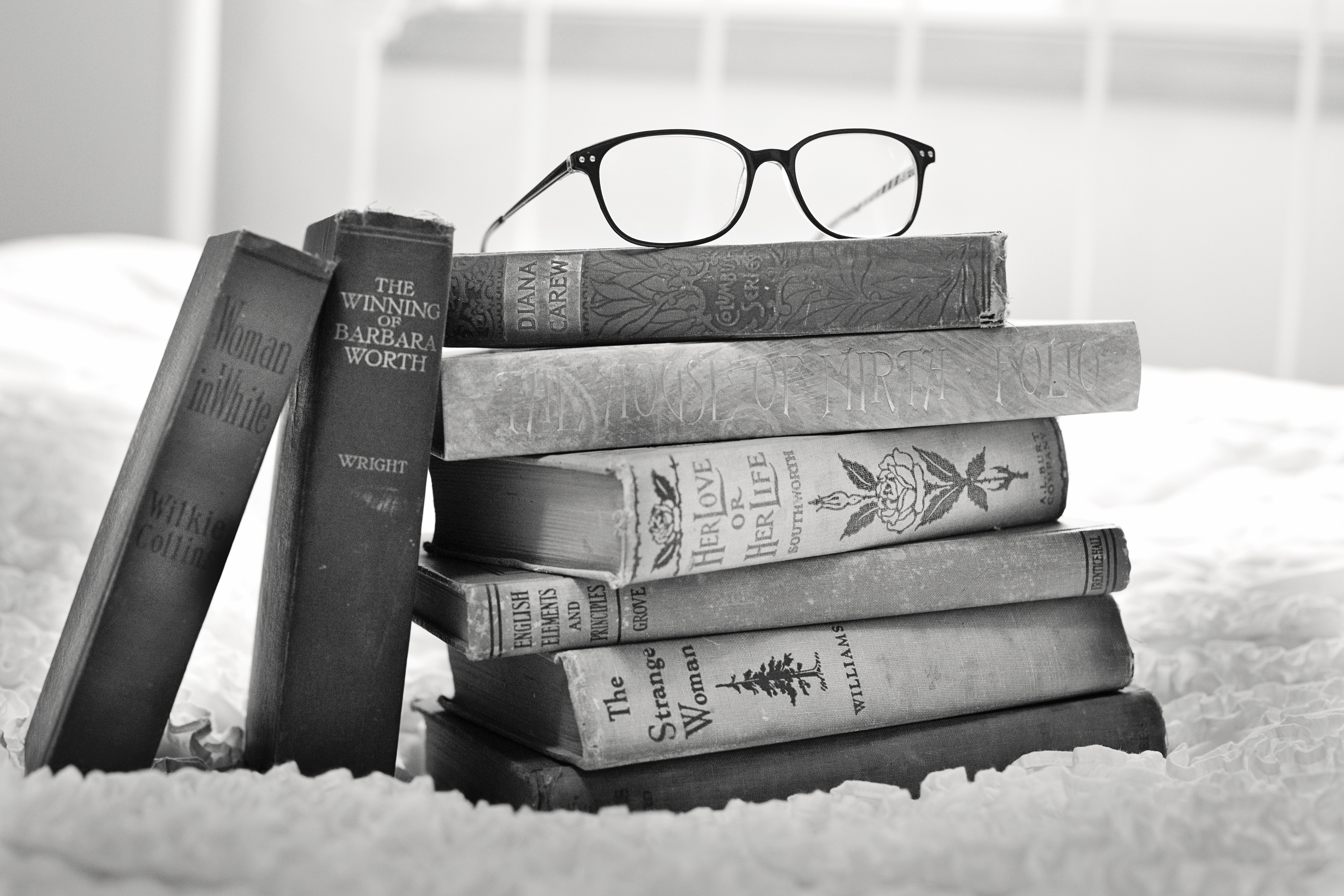 Grayscale Photo of Eyeglasses on Pile of Books · Free Stock
