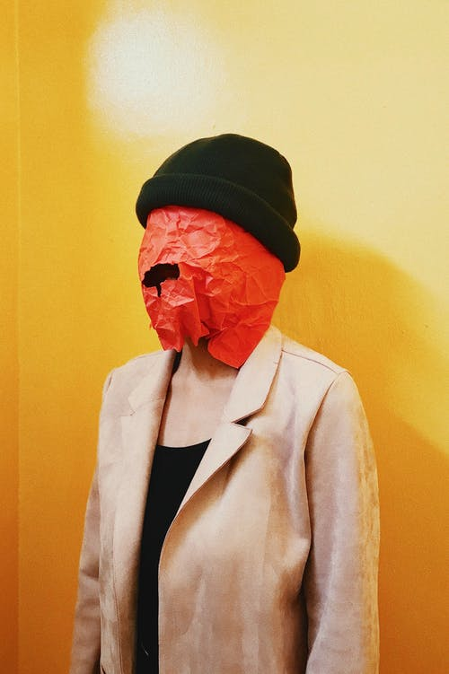 Woman Covered With Paper on the Head standing Beside Yellow Wall