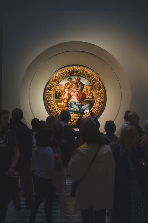 Silhouettes of exhibition visitors enjoying Donni Madonna painting by Michelangelo placed in medieval golden frame and hanging on museum wall