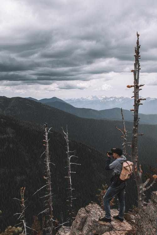 Man On Top Of A Mountain Taking Picture Of The View