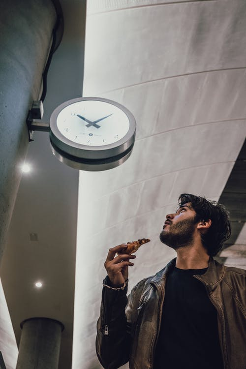 Low Angle Photo of Man Looking Towards the Clock