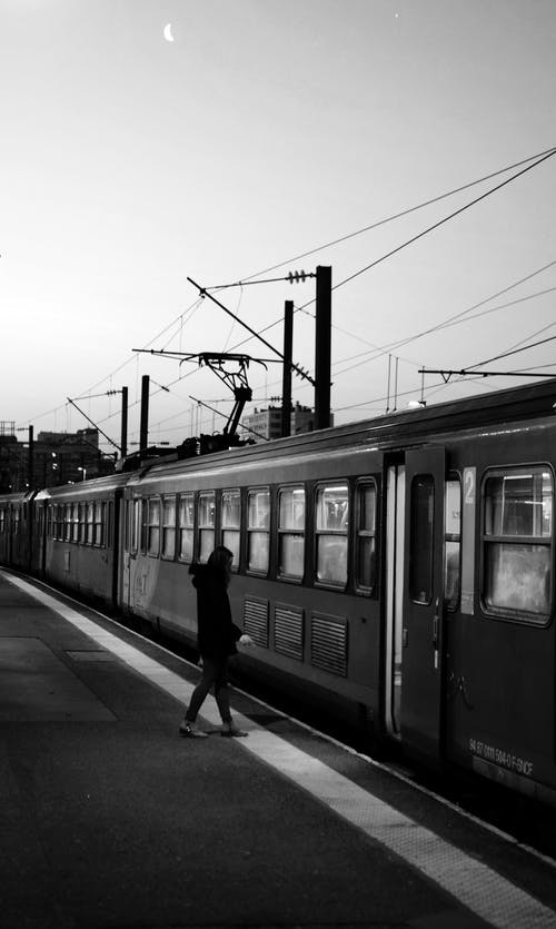Monochrome Photo of Person Standing Beside Train