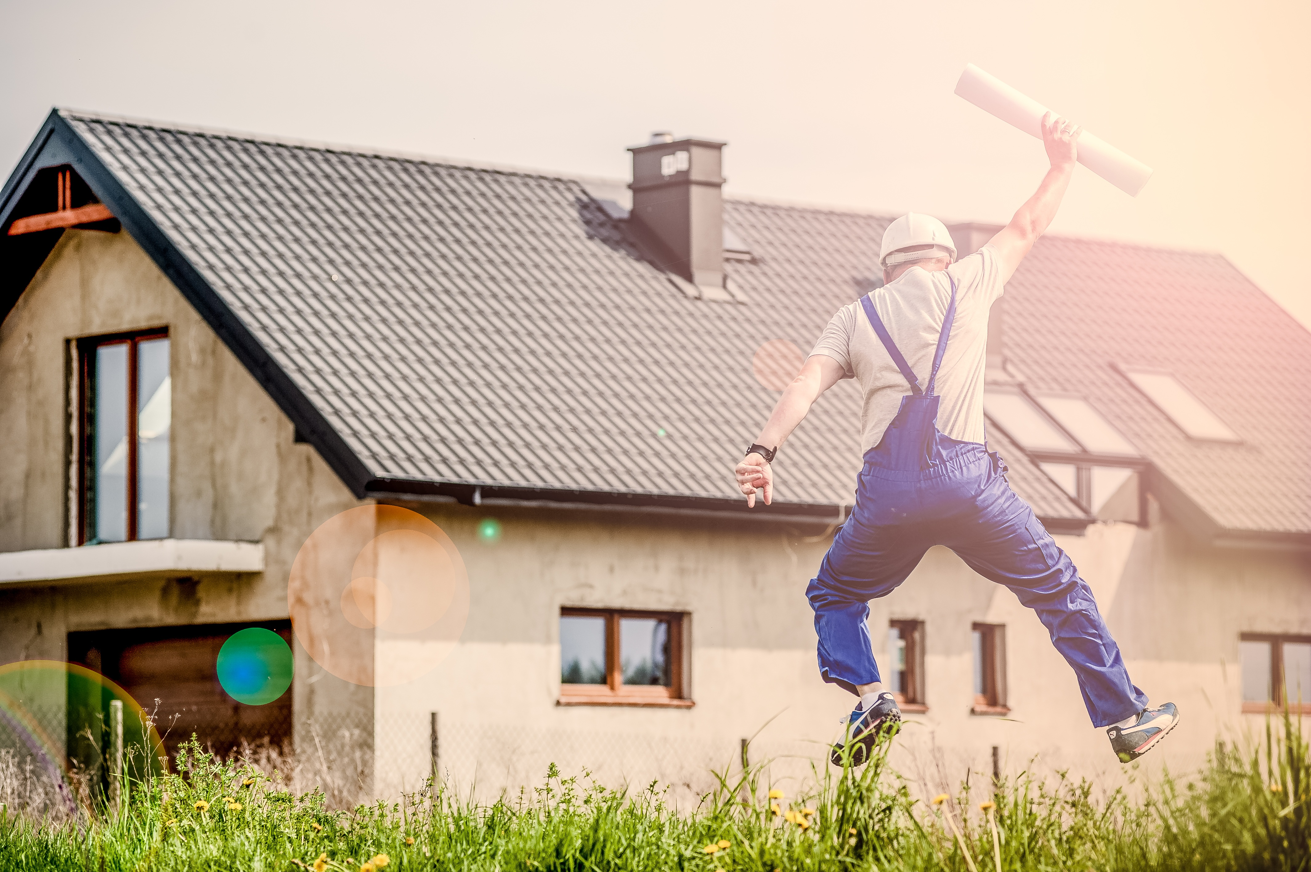 Man Jumping in Front of House