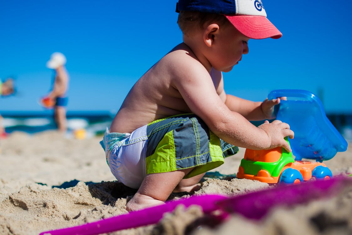 Toddler Playing Plastic Toy Car on Beach