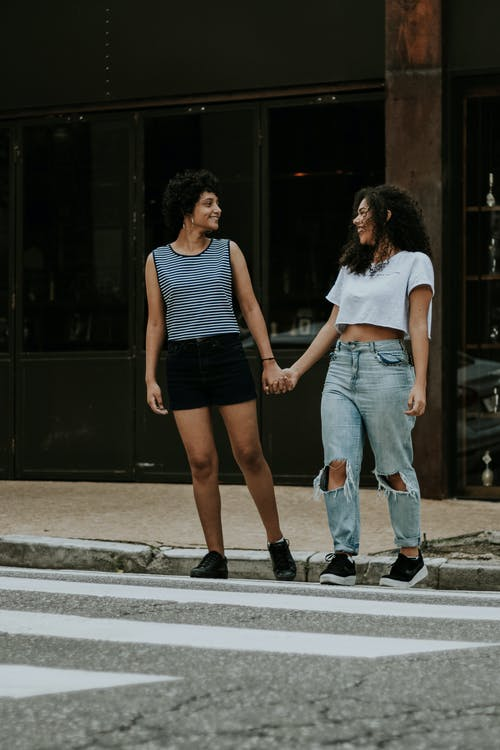 Photo of Two Women Walking on Pedestrian Crossing