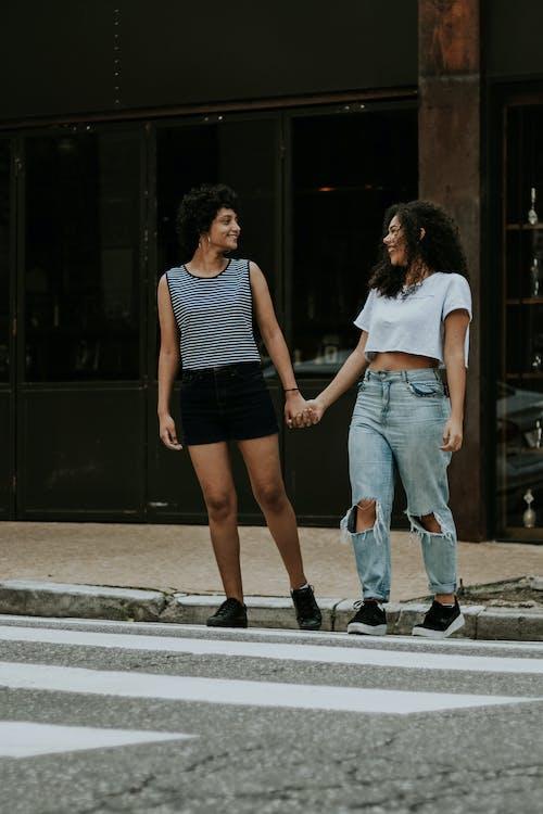 Photo of Two Women Walking on Pedestrian Crossing