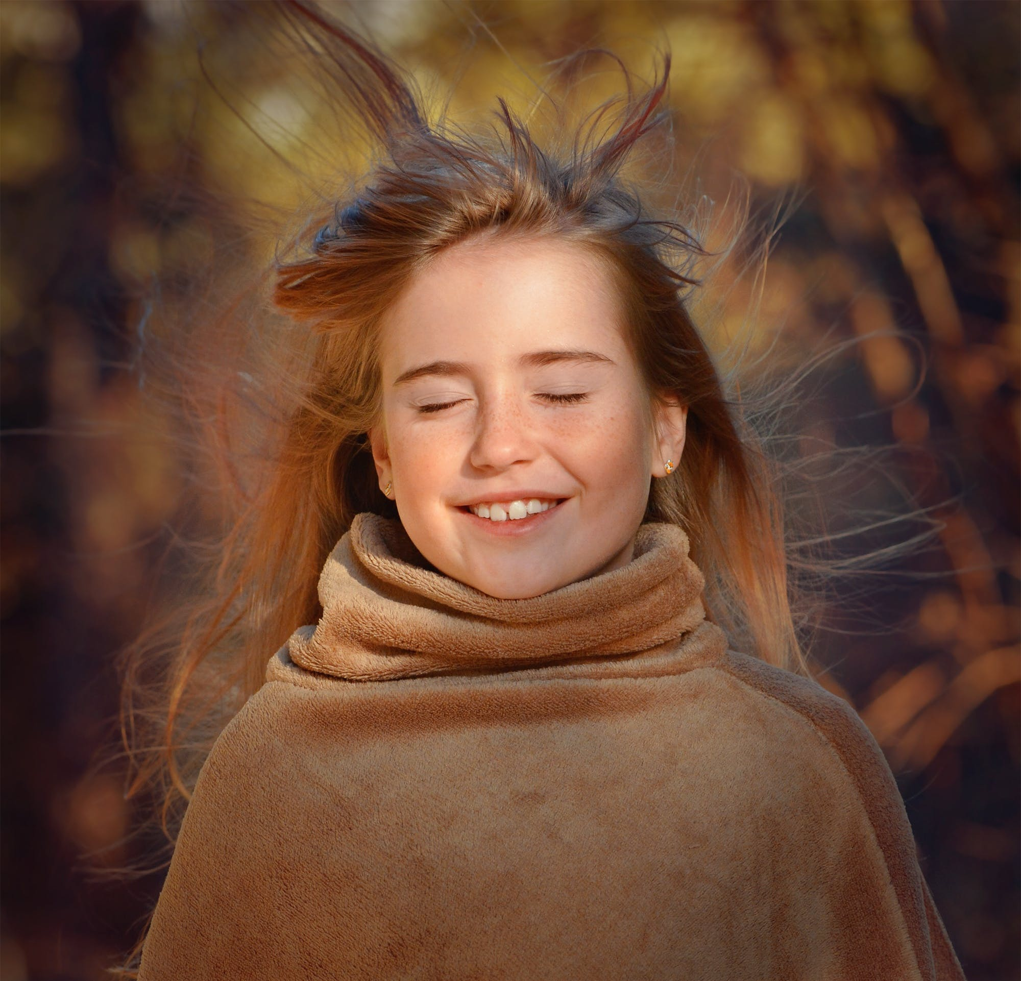 Hair Blowing on Smiling Girls Face Wearing Brown Coat