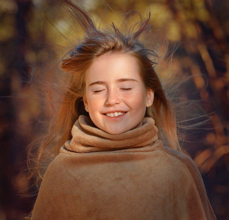 Hair Blowing on Smiling Girls Face Wearing Brown Coat