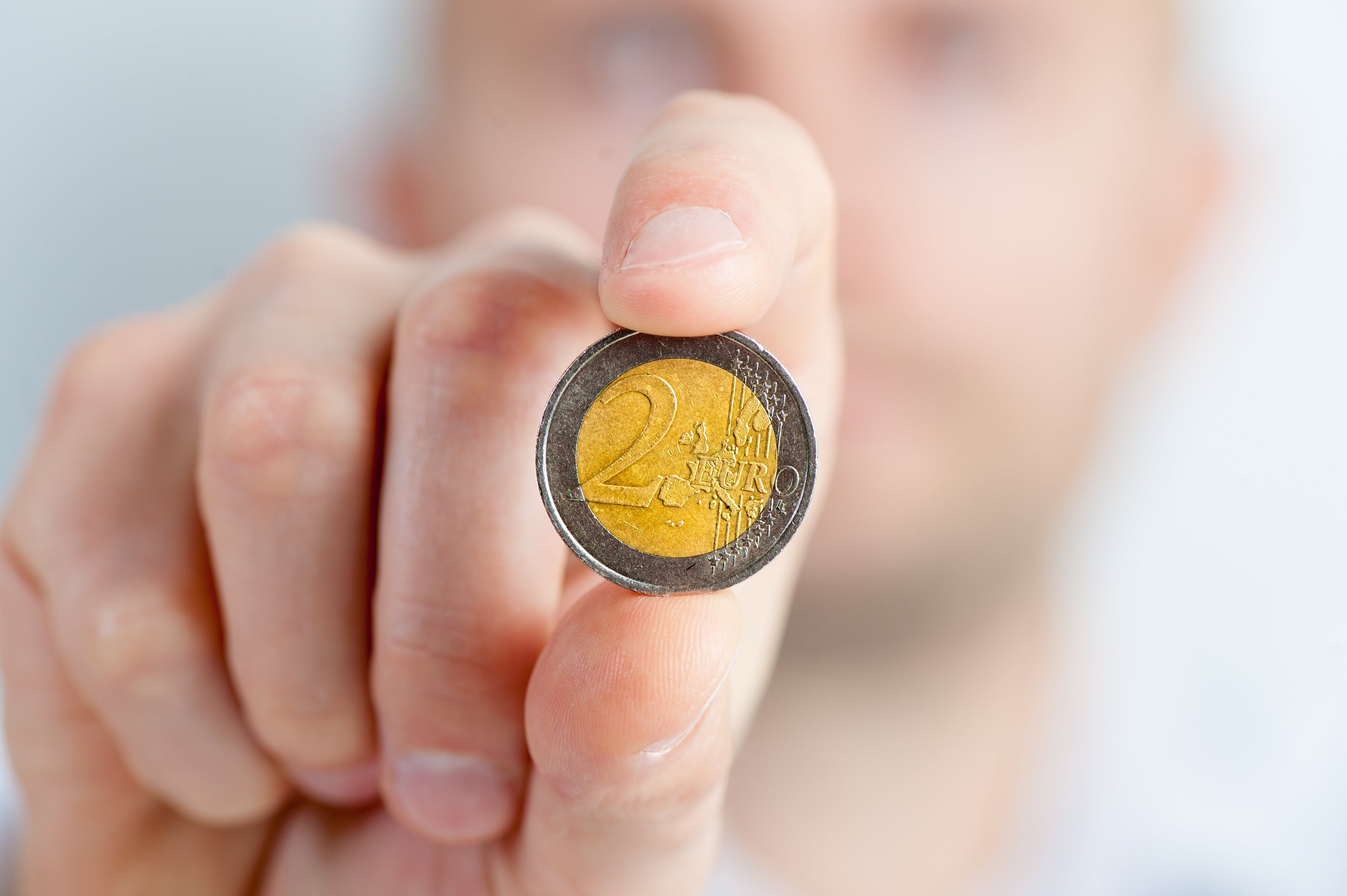 Person Holding a Gold and Silver Round Coin
