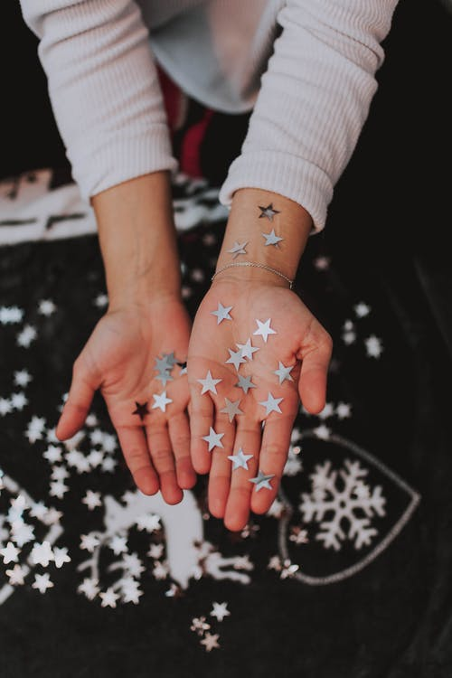 Crop woman with silver paper stars decorating Christmas toys