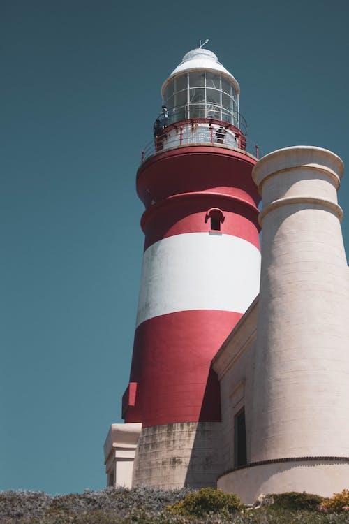 Lighthouse tower on seashore against blue sky