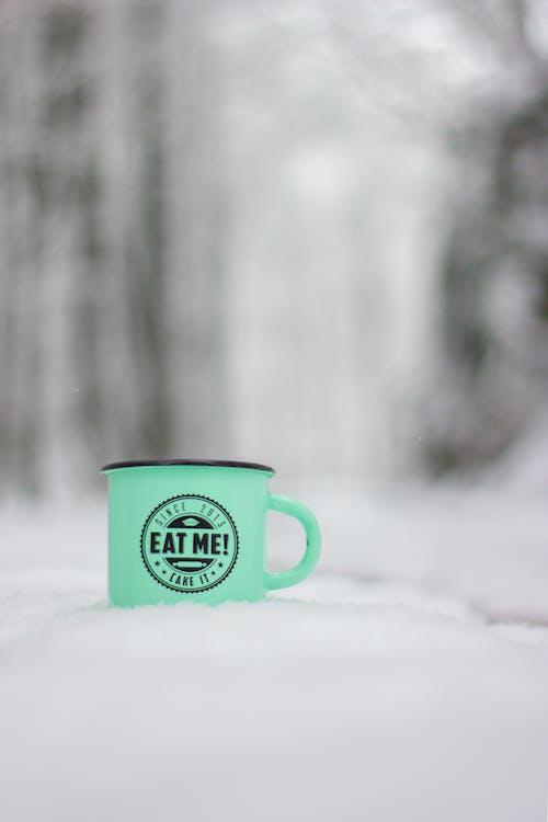 Green and White Ceramic Mug on Snow Covered Ground