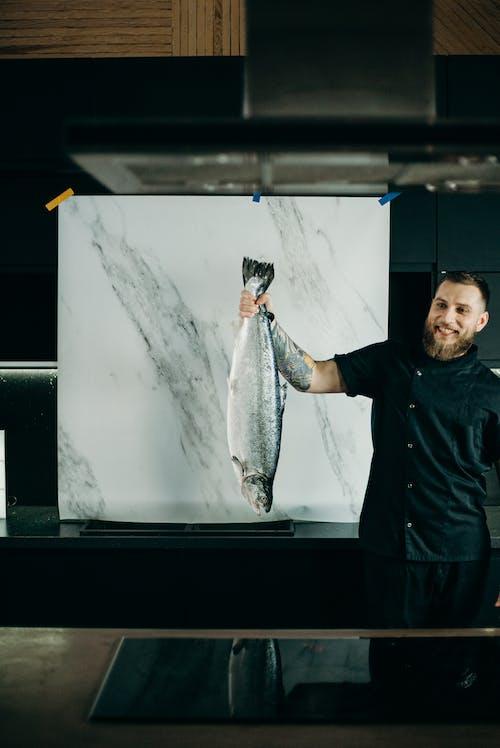 Man Holding Grey Fish