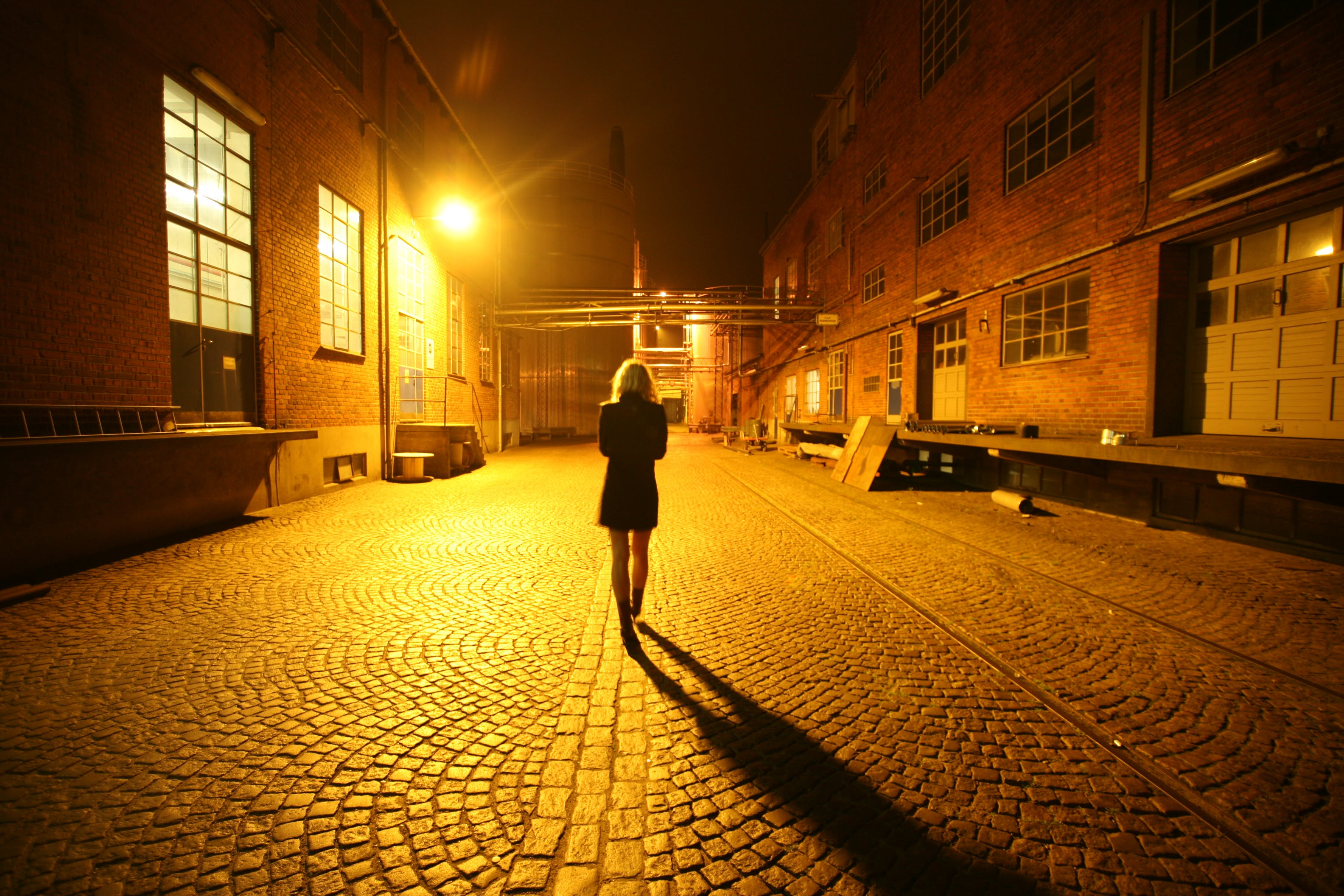 Woman Walking on Street at Night