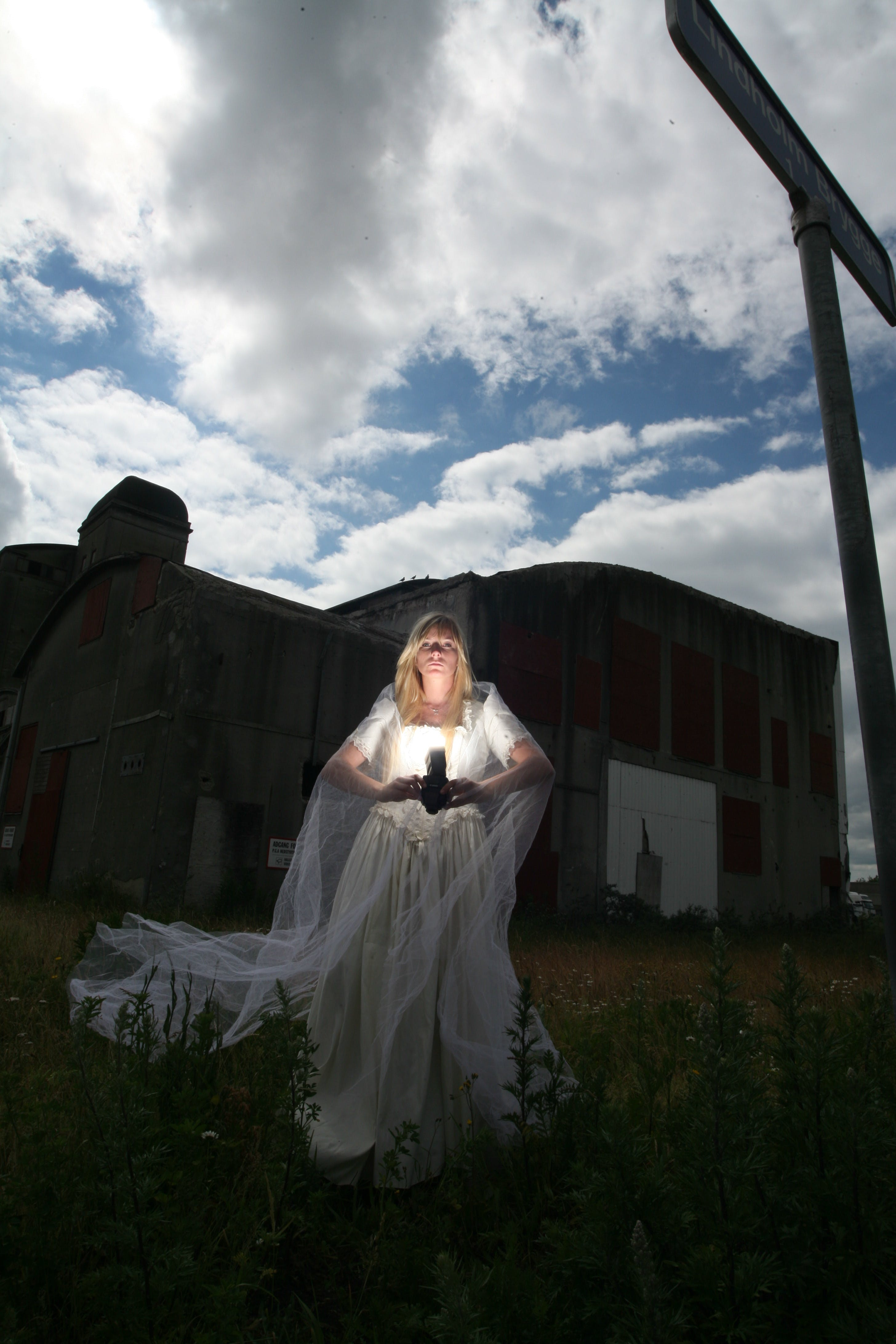 Woman in White Dress Holding Flashlight on Outdoors at Night