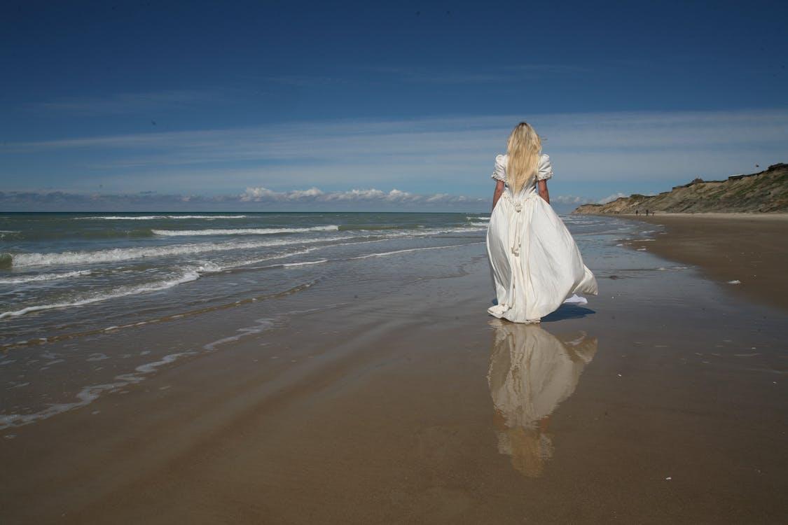 Woman Walking Near Shore