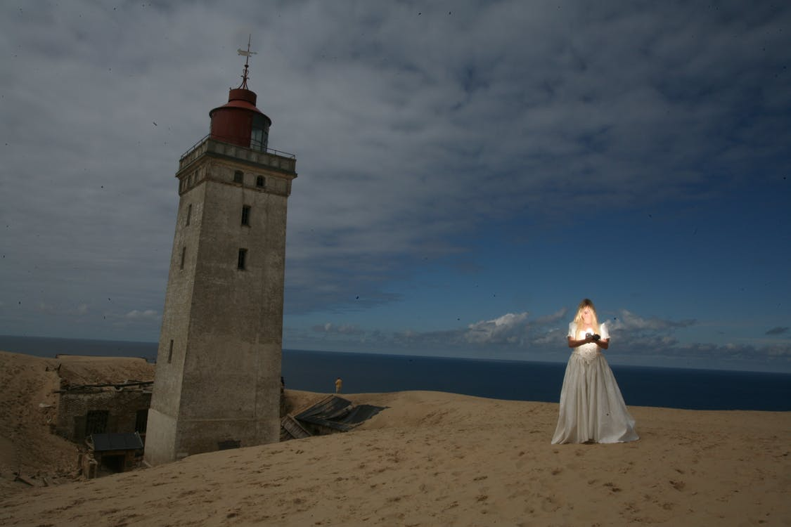 Woman Standing Near Gray Lighthouse