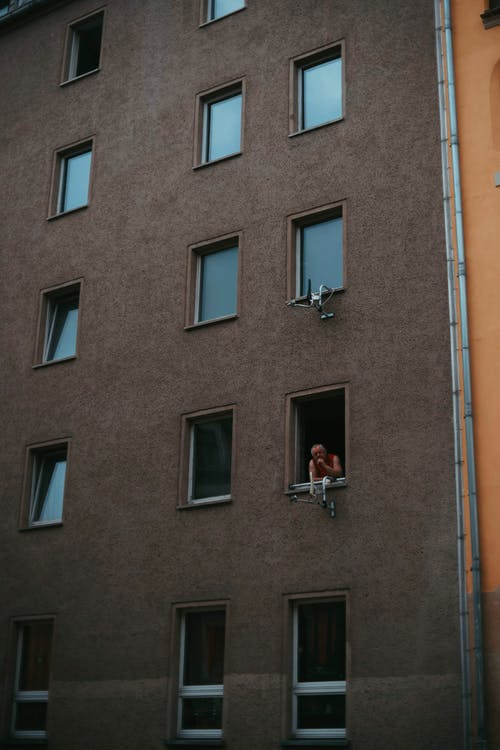Person in simple apartment building window